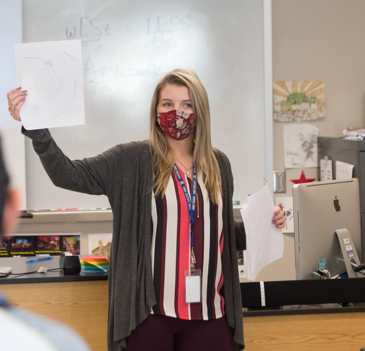 A student teacher holds up a paper in front of a class